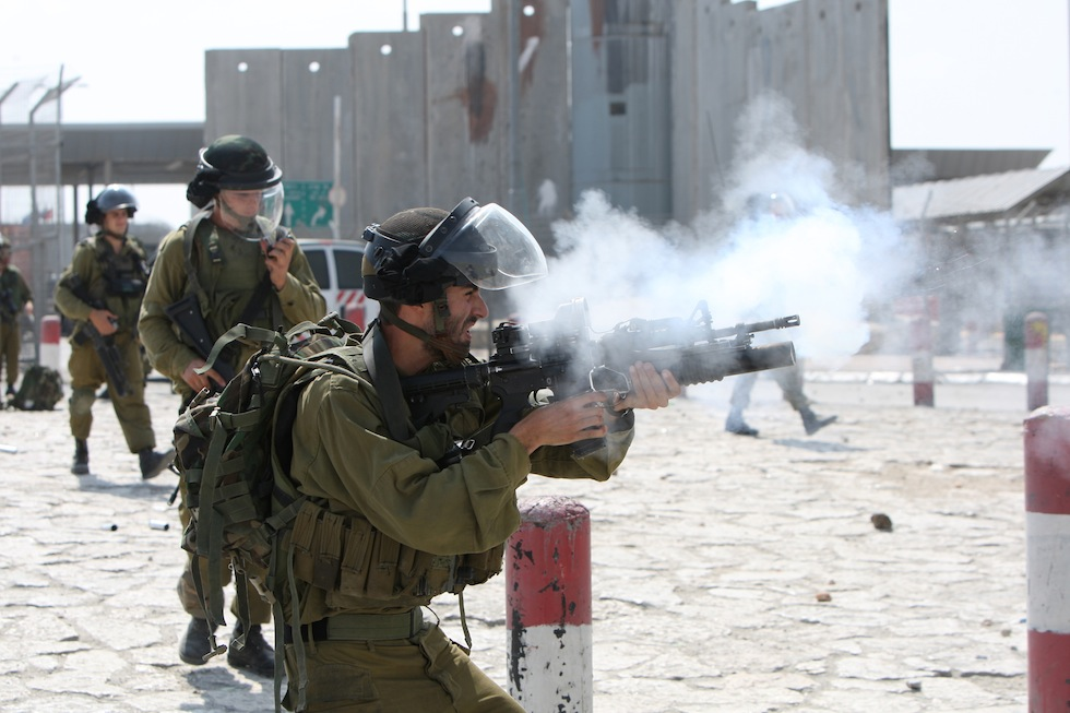Israeli soldiers fire tear gas canisters