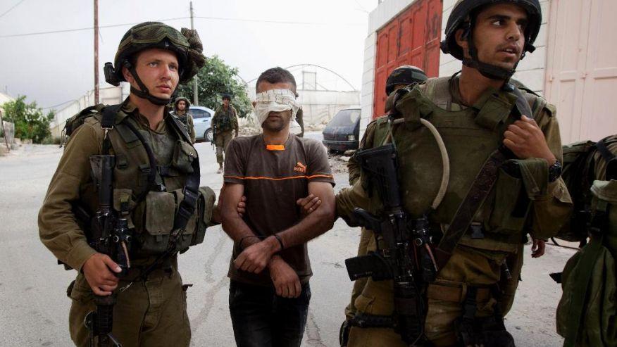 L'esercito israeliano arresta un palestinese in un villaggio vicino Hebron, il 21 giugno (Foto: AP Photo/Majdi Mohammed)