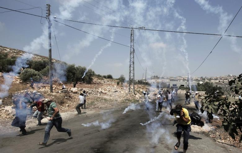 Tear gas canisters land as Palestinian stone throwers clash with Israeli security forces following a weekly protest against the expropriation of Palestinian land by Israel in the village of Kfar Qaddum, near the northern city of Nablus, in the occupied West Bank on July 4, 2014. (Photo: AFP-Jaafer Ashtiyeh)