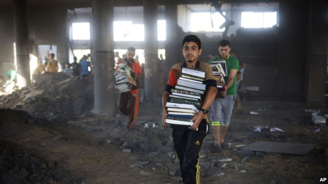 Ragazzi palestinesi portano fuori libri dalla moschea distrutta di Zeitoun, a Gaza City (Foto: AP)