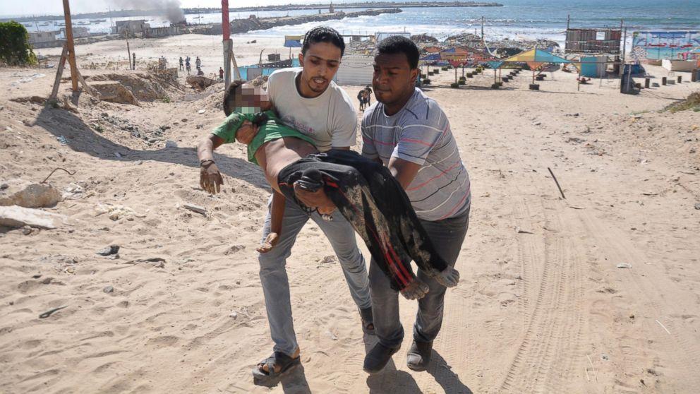 Bambino ferito da cannonata israeliana sulla spiaggia di Gaza (foto Mohammed Talatene, Reuters)