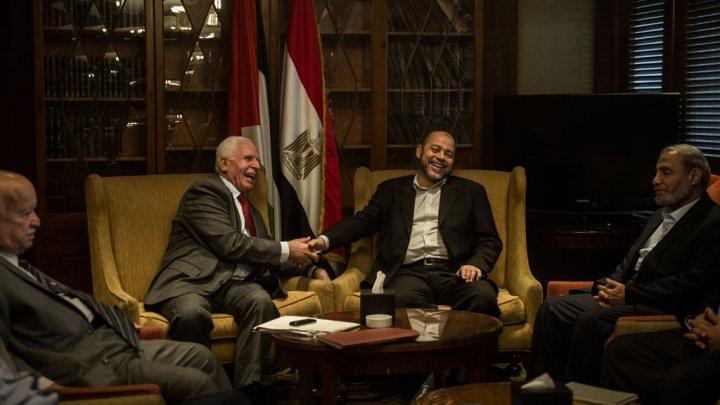Da sinistra, il capo negoziatore di Fatah Azzam al-Ahmad stringe la mano al capo dell'ufficio politico di Hamas Moussa Abu Marzouk al Cairo (Foto: Khaled Desouki/AFP)