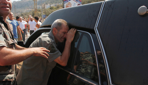 A father of a Lebanese soldier captured by hard-line Syrian Islamists reacts next to a hearse carrying the coffin of another soldier, Ali al-Sayyed, who was beheaded by Islamic State militants in Arsal, during his funeral in Qalamoun, in Akkar, Sept. 3, 2014. (photo by REUTERS/Omar Ibrahim. Source: al-Monitor)