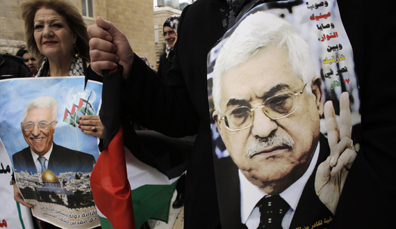 Palestinians hold posters depicting President Mahmoud Abbas during a rally in the West Bank town Bethlehem, March 17, 2014.  (photo by REUTERS/Ammar Awad. Source: al-Monitor)