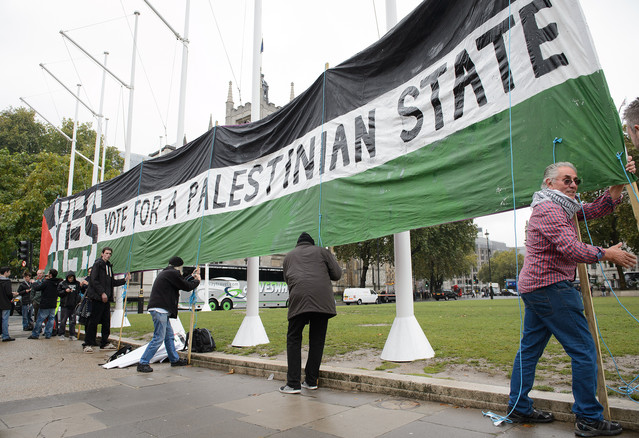 Pro-Palestinian supporters position a giant banner in Parliament Square,  London on Oct. 13, 2014. (Photo: Leon Neal/AFP/Getty Images)