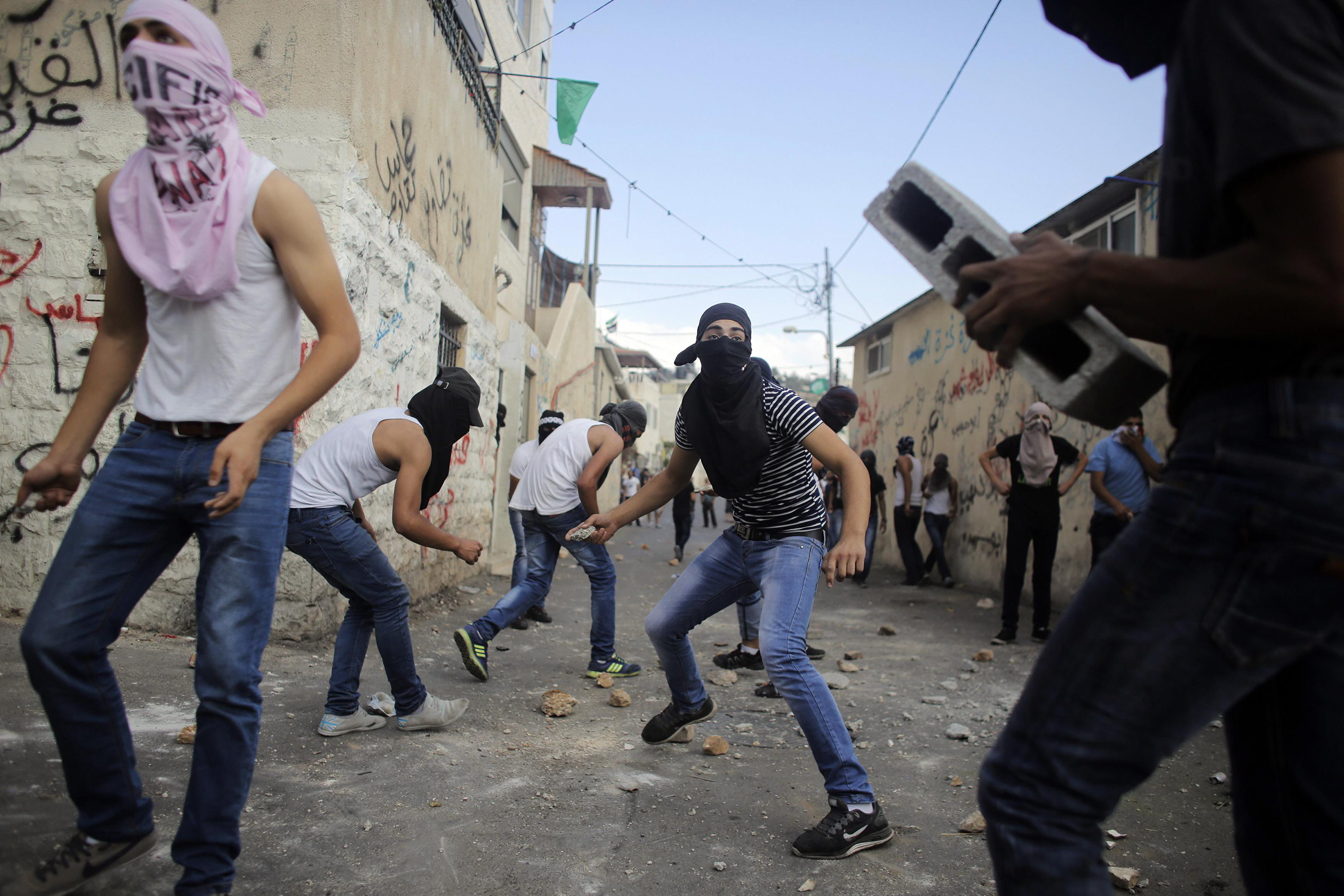 Palestinians hurl stones during clashes with Israeli police in the East Jerusalem neighbourhood of Wadi Joz