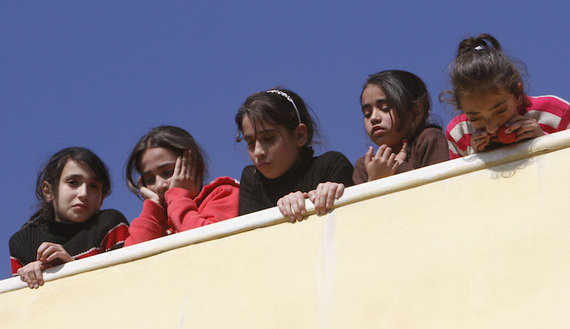 Palestinian girls watch as mourners carry the body of 17-year-old Palestinian Imam Dwikat, who was shot dead by Israeli troops, during his funeral in the West Bank village of Beita near Nablus