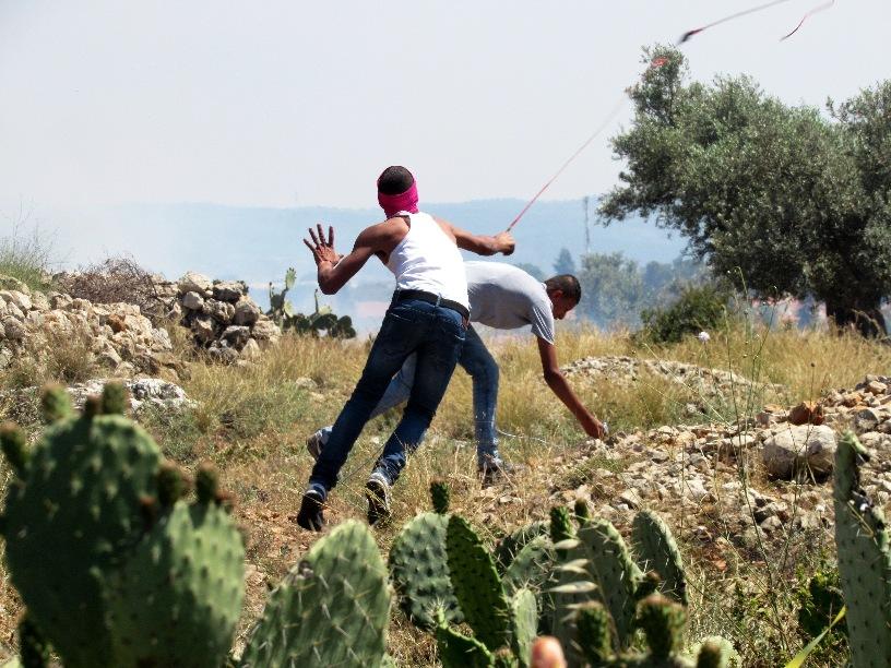 Lancio di pietre durante la manifestazione di commemorazione della Nakba, lo scorso 15 maggio, nel villaggio di Ni'lin (Foto: Chiara Cruciati/Nena News)