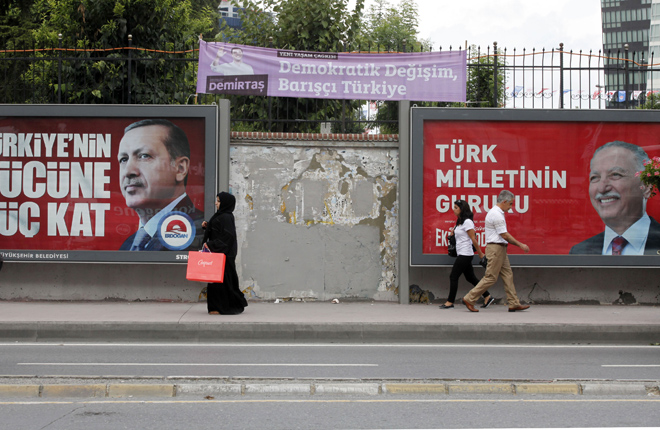 People walk past election posters  in Istanbul