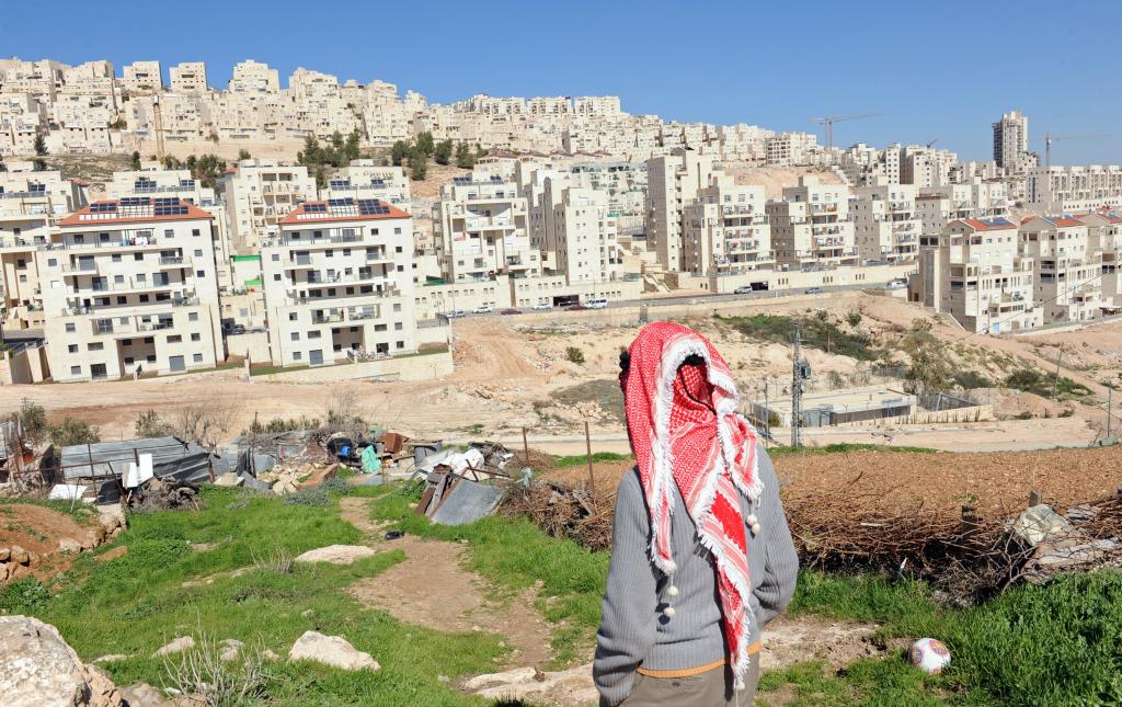 Un palestinese osserva una colonia israeliana in Cisgiordania. Foto Debbie Hill UPI