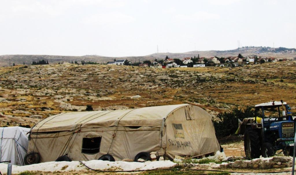 Il villaggio di Susiya, dietro una colonia israeliana (Foto: Chiara Cruciati)