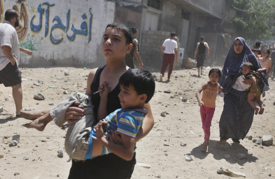 Gaza, civili in fuga dalle bombe (foto Reuters)