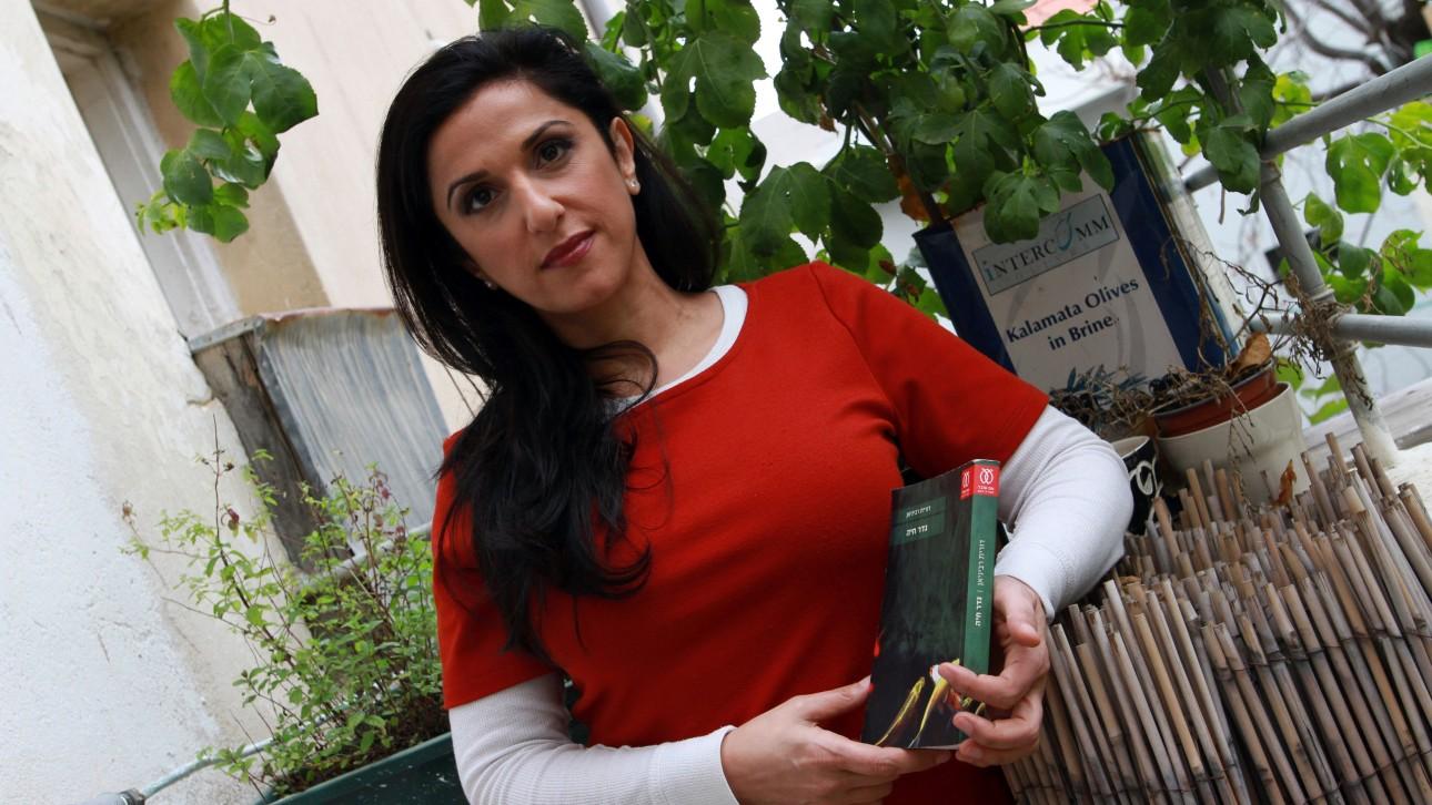 """La scrittrice Dorit Rabinyan, con in mano una copia del suo rmanzo """"Borderlife"""" (foto GIL COHEN MAGEN/AFP/Getty Images)"""