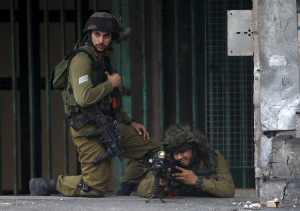 Israeli army soldier aims his weapon at Palestinians during clashes in the West Bank city of Hebron