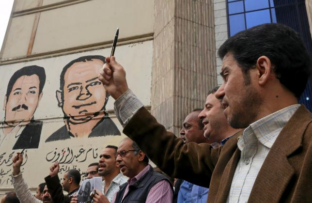 A journalist holds up a pen during a protest against the detention of journalists, in front of the Press Syndicate in Cairo