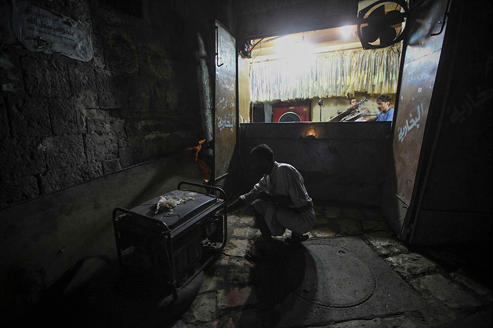 Un uomo cerca di far funzionare un generatore a Sana'a (Foto: Alessandria Masi e Dustin Drankoski/Vocativ.com)