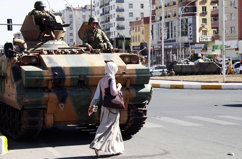 Una donna kurda di fronte a un tank dell'esercito turco nel sud est del paese (foto LaPresse)
