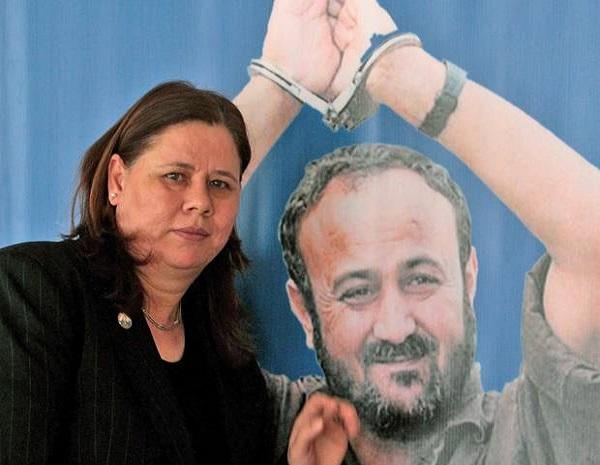 Fadwa Barghouti accanto a un poster con l'immagine del marito Marwan