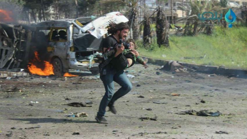 Un'immagine diventata subito simbolica: il fotografo Abd Alkader Habak porta in salvo un bambino ferito nell'attacco di Rashidin