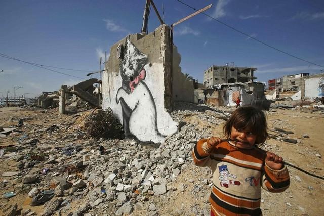 GAZA. Una bambina tra le macerie accanto a un murale dello street artist Banksy