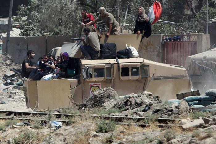 Sfollati portati via dall'esercito iracheno a Mosul ovest (Foto: Marius Bosch/Reuters)