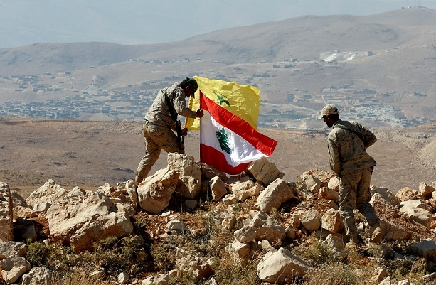 Hezbollah fighters put Lebanese and Hezbollah flags at Juroud Arsal, Syria-Lebanon border