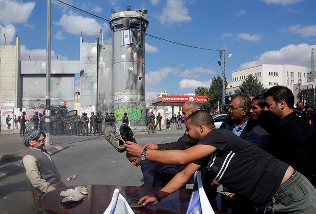 Betlemme. Palestinesi, che manifestano nei pressid el Muro israeliano, colpiscono un manichino somigliante ad Arthur Balfour (foto Reuters)