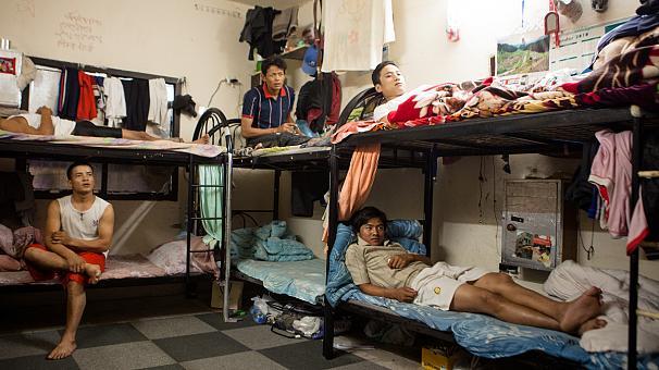 Lavoratori asiatici nei compound dove sono costretti a vivere