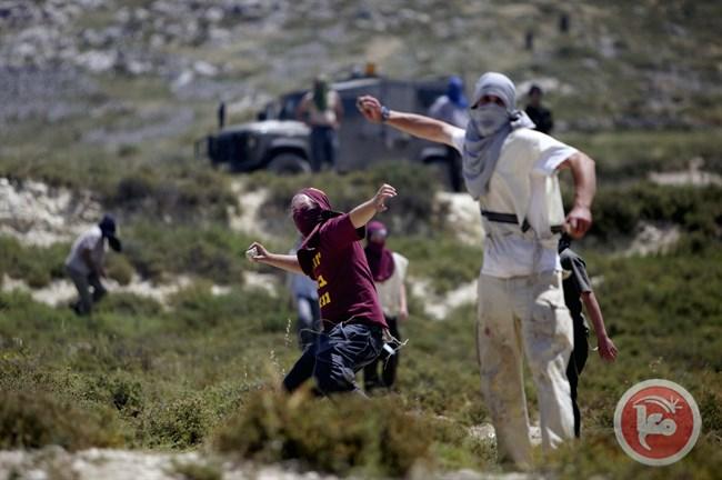 Coloni lanciano pietre contro palestinesi, vicino ad una camionetta dell'esercito (Foto: Ma'an)