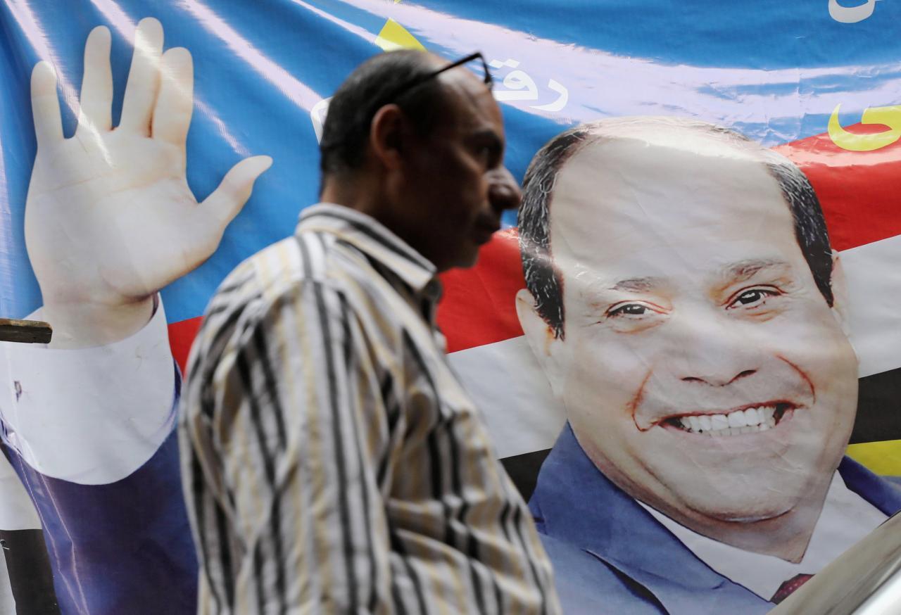 Un uomo cammina vicina al poster di al-Sisi al Cairo (Foto: Reuters/Mohamed Abd El Ghany)