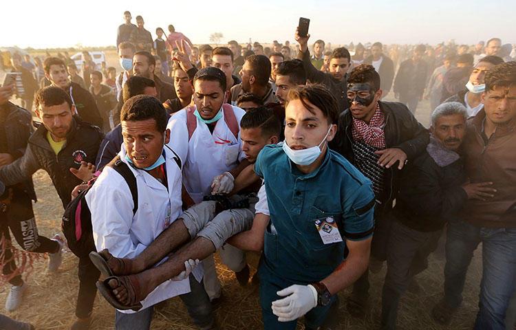 Palestinese ferito al confine tra Gaza e Israele. (Foto: Reuters/ Ibrahim Abu Mustafa)
