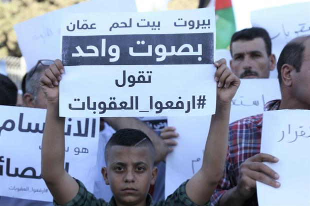 """Il cartello recita in arabo: """"Beirut, Betlemme e Amman con una voce dicono: 'Togliete la sanzioni' """" (Foto: MEE/Akram al-Wara)"""