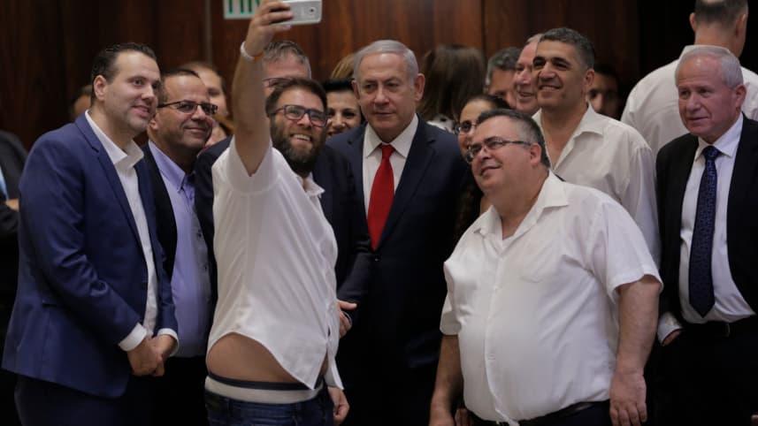 Il premier Netanyahu e un gruppo di deputati della maggioranza di destra festeggiano con un selfie l'approvazione della legge (foto di Olivier Fitoussi)