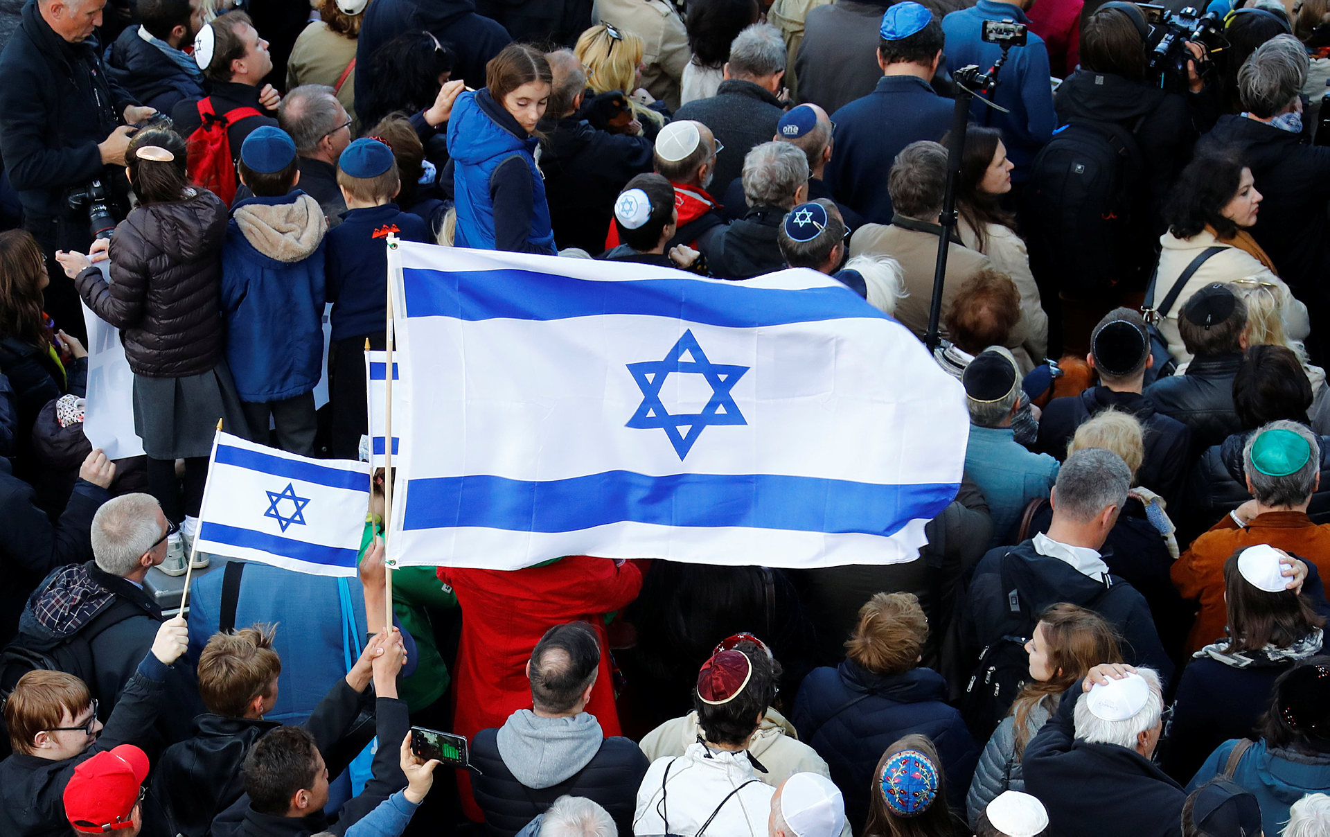 An Israeli flag is held during a demonstration in front of a Jewish synagogue in Berlin