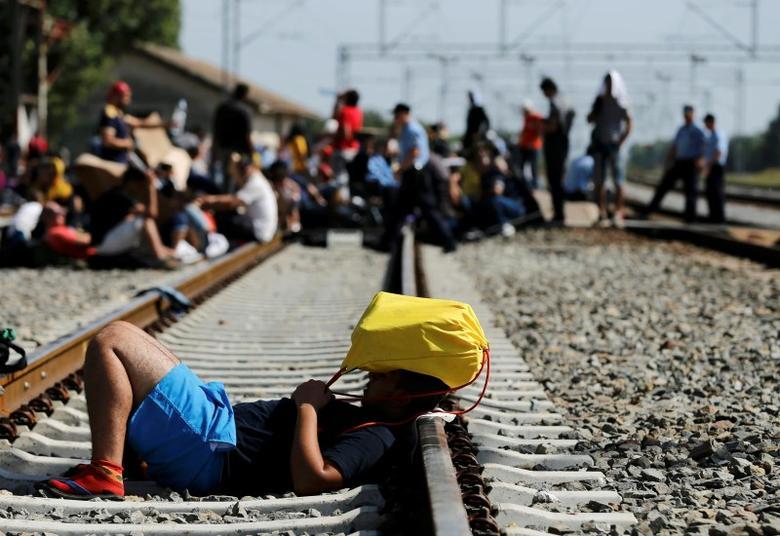 Migrante steso sui binari a Tovarnik (Croazia) nel settembre 2015 (Foto: REUTERS/Antonio Bronic)