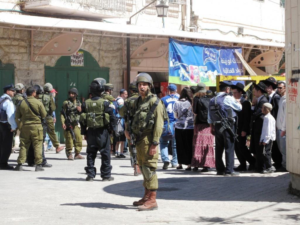 Coloni e soldati israeliani a Shuhada Street, Hebron  (Foto: Chiara Cruciati/Nena News)