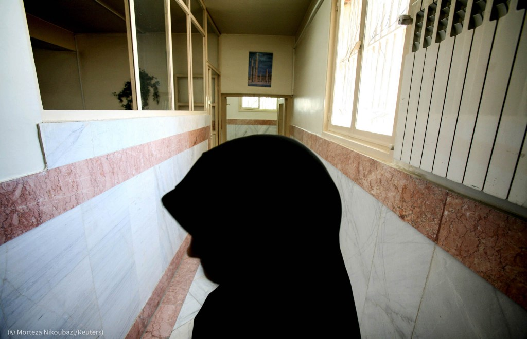 A female prison guard stands along a corridor in Tehran's Evin prison June 13, 2006. Iranian police ..