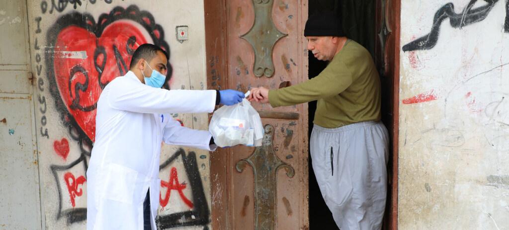 Un membro dell'Unrwa consegna a casa dei medicinali, Gaza (Foto: Unrwa/Khalil Adwan)